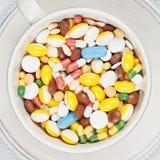 Weißes Cup auf der Platte füllte mit Pillen Stockbilder
