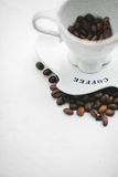 Weißes Cup mit Körnern des Kaffees und des Saucer Stockfotografie