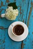 Weißes Cup mit Kaffee mit weißem Hydrangea stockbild