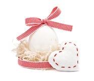 Weißes Ei in einem Nest mit rotem Band und Bogen Stockfotos