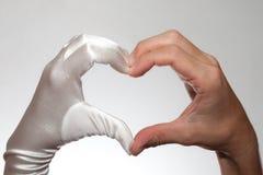 Weißes elegantes Herz formte den Handschuh der Frau und die Hand des Mannes, die auf weißem Hintergrund lokalisiert wurden Stockfoto