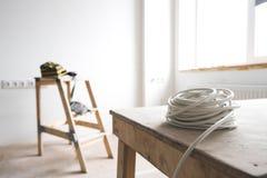 Weißes elektrisches Kabel steht auf der Leiter der Ziege innerhalb der Wohnung und der Reparatur still Stockfotos