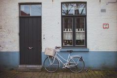 Weißes Fahrrad, das nahe der Ziegelsteinfassade des Hauses steht Stockfotos