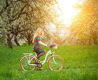 Weißes Fahrrad der Frauenreitweinlese mit Blumenkorb Lizenzfreie Stockfotos