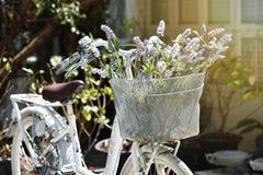 Weißes Fahrrad der Weinlese mit Blumenstrauß von Blumen im Korb Lizenzfreies Stockbild