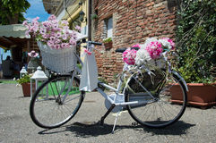 Weißes Fahrrad klassisch mit Blumendekorationen lizenzfreie stockfotografie