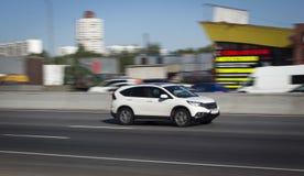 Weißes Familienauto geht schnell auf Straße stockfotos