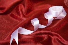 Weißes Farbband auf Rot drapieren Stockbild