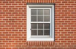 Weißes Fenster auf einer Wand des roten Backsteins, Sonne reflction auf dem Glas Lizenzfreies Stockbild