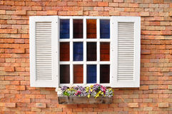 Weißes Fenster auf Wand- und Farbglasfallblumentopf des roten Backsteins Stockfotografie