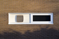 Weißes Fenster in der Brown-Backsteinmauer Stockfotografie