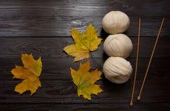 Weißes Garn, hölzerne Nadeln, Gelb verlässt auf dunklem Holztisch Stockbild