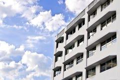 Weißes Gebäude, blauer Himmel mit Wolken lizenzfreies stockfoto