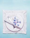 Weißes Gedeck mit Schlagmal, Tischbesteck, Spitze Doilyserviette und dem Blumenblatt blüht auf blauem schäbigem schickem hölzerne Lizenzfreie Stockbilder