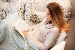 Weißes gemütliches Bett und schönes ein Mädchen, ein Buch am Abend, Konzepte des Hauses und Komfort lesend Stockfotografie