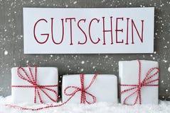Weißes Geschenk mit Schneeflocken, Gutschein bedeutet Beleg Lizenzfreie Stockfotos