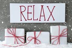 Weißes Geschenk mit Schneeflocken, Text entspannen sich Stockbild