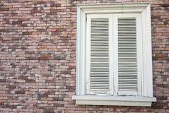 Weißes geschlossenes Fenster auf Backsteinmauer Stockbild
