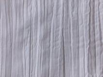 Weißes Gewebe mit einem zerknitterten Effekt und vertikalen Falten stockfoto