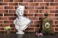 Weißes Gipsfehlschlag-Skulpturporträt eines jungen Mannes und der alten Uhr auf dem Tisch, Details des Luxusinnenraums im Klassik Stockfoto