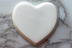 Weißes glattes Porzellanherz auf einer Marmorbeschaffenheit Hochzeitskarte; Eine Liebesanmerkung stockbilder