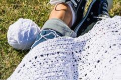 Weißes Häkeln auf den Frauen nees, die auf dem Gras sitzen Stockfoto