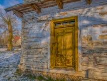 Weißes hölzernes Blockhaus mit gelber Tür Lizenzfreies Stockfoto