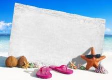 Weißes hölzernes Brett mit anderen Gegenständen durch den Strand lizenzfreies stockbild