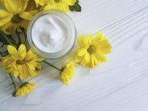 Weißes hölzernes der kosmetischen Feuchtigkeitscremecreme Wellnessgänseblümchengelbchrysanthemenprodukt-Kamille stockbilder