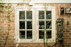 weißes hölzernes Fenster auf Backsteinmauer Stockfoto