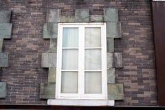 Weißes hölzernes Fenster auf Backsteinmauer Stockbild