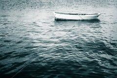 Weißes hölzernes Fischerboot schwimmt auf ruhiges Meer Lizenzfreie Stockbilder