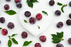 Weißes hölzernes Herz und reife saftige Pflaumen auf einem weißen Hintergrund Lizenzfreie Stockfotografie