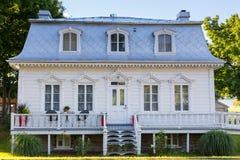 Weißes hölzernes Landhaus des Regency-Stils mit silbernem Metallmansardendach stockbilder
