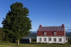 Weißes hölzernes Landhaus mit rotem Zinndach stockfotos