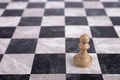 Weißes hölzernes Pfand auf Schachbrett Stockfotos