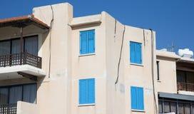 Weißes Haus mit blauen Fensterläden und hölzernem Balkon Stockfotos