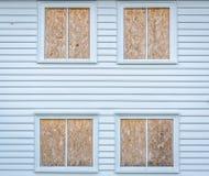 Weißes Haus mit geschlossenen Fenstern durch Bauholz Stockfotos