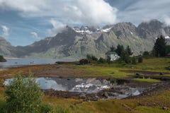 Weißes Haus und Spiegelsee mit der Ansicht, zum Berge und Meer im Norwegen am Sommer zu schneien Lizenzfreie Stockfotos
