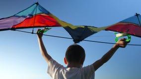 Weißes Hemd des kleinen Jungen der hinteren Ansicht hob über seinen Hauptdrachen auf blauem Himmel des Hintergrundes an stock footage