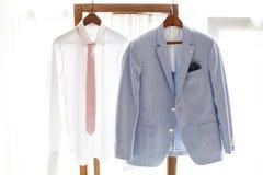 Weißes Hemd und grauer Anzug des Bräutigams hängend am Aufhänger Stockfoto