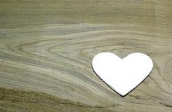 Weißes Herz auf hölzernem Hintergrund Stockfotos