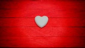 weißes Herz auf rotem hölzernem Steigungsunschärfehintergrund Stockfotografie