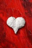 Weißes Herz auf rotem Hintergrund Lizenzfreie Stockbilder
