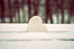 Weißes Herz auf schneebedeckter Parkbank stockfoto