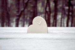 Weißes Herz auf schneebedeckter Parkbank Symbol der reinen Liebe stockfotografie