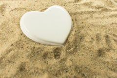wei?es Herz, das im Sand auf dem Strand liegt lizenzfreie stockfotografie