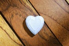 Weißes Herz mit hölzernem Hintergrund lizenzfreie stockfotografie