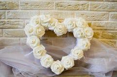 Weißes Herz mit weißen Rosen und Bergkristallen stockfoto