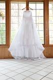 Weißes Hochzeits-Kleid, das durch Window hängt Stockbild